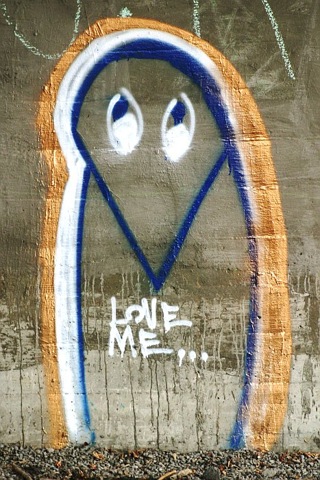 "graffiti of a bird (a penguin) with the words ""love me"" on its round belly"